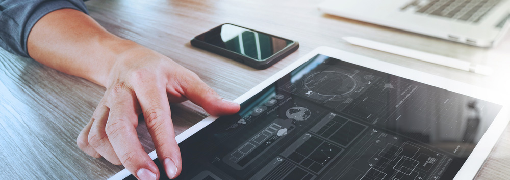 Website-designer-working-digital-tablet-and-computer-laptop-with-smart-phone-and-graphics-design-diagram-on-wooden-desk-as-concept